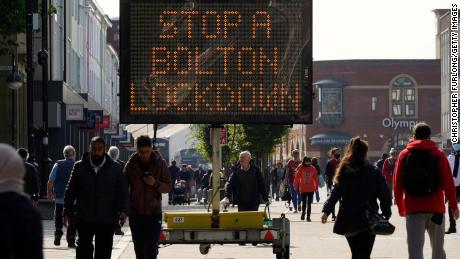 People walk past an electronic sign in Bolton, England, on September 17.