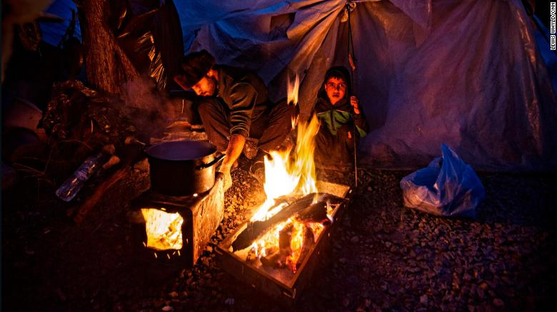 People gather around a fire for warmth in the Moria refugee camp in Lesbos, Greece in February 2020.
