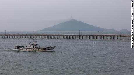 A fishing boats sails past a bridge on Yeonpyeong Island, South Korea, on Friday, June 26, 2020. On the sleepy island of Yeonpyeong, the threat of conflict is constant with North Korean coastal howitzers just 11 kilometers (7 miles) away and propaganda banners visible through binoculars. There have been several military clashes in the contested maritime boundary off the west of the peninsula since 1999, making it a possible ignition point for a major conflict that could draw in the U.S. and China  the two biggest allies for the rival Koreas. Photographer: SeongJoon Cho/Bloomberg via Getty Images