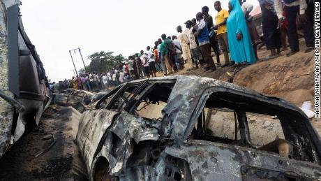 Bystanders look on at the wreckage of a truck that caught fire in Lokoja, Nigeria, on September 23, 2020.