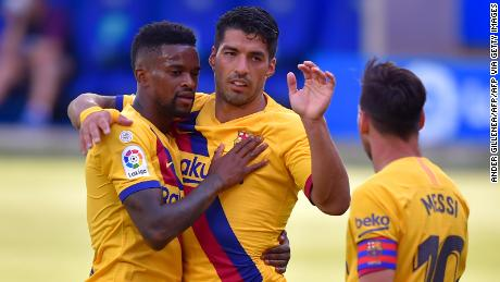 Suarez ceelbrates a Barcelona goal with Lionel Messi and Nelson Semedo last season.