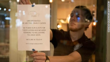 A man puts a sign in the window of the Corner House pub in Cardiff, Wales in March.