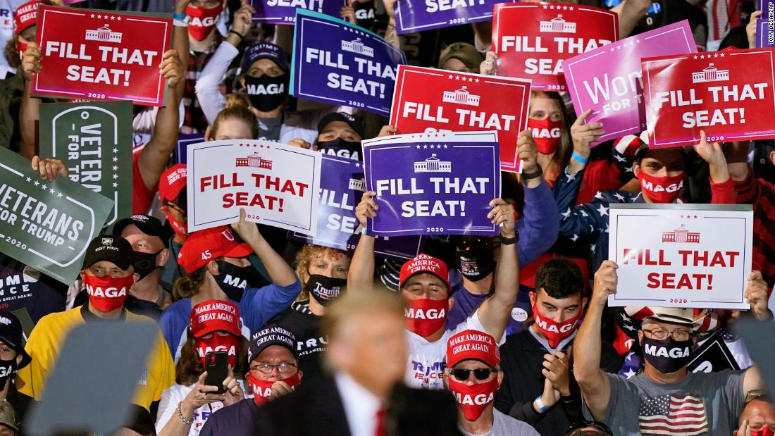Trump supporters hold up signs as he speaks at a campaign rally in Swanton, Ohio, on September 21.