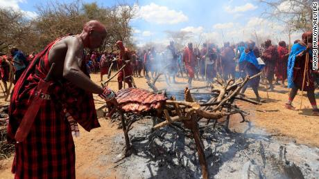 Maasai youth roast meat for the celebrants before attending the rites of passage initiation ceremony. The event was initially postponed due to the coronavirus disease outbreak in Maparasha hills of Kajiado, Kenya.