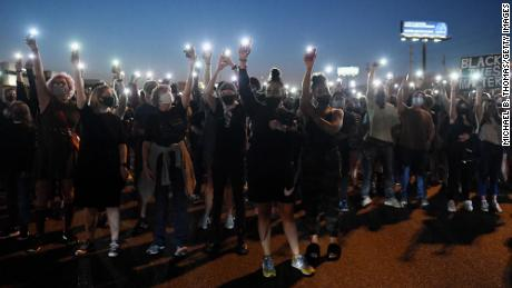 Protesters light up their phones during a protest Thursday in St Louis, Missouri, in response to a Kentucky grand jury not bringing charges against police officers in the death of Breonna Taylor.