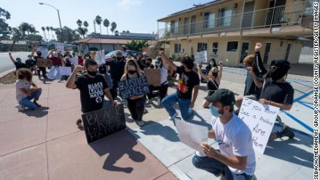 Protesters pause for a moment outside Hotel Miramar in San Clemente, California, on Thursday