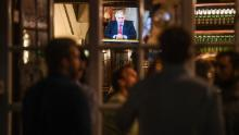 London's Westminster Arms pub drinkers watch British Prime Minister Boris Johnson deliver a televised speech to the nation on Tuesday.