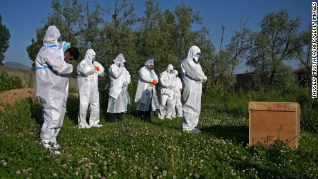 Relatives wearing personal protective equipment offer funeral prayers for a woman who died from the coronavirus, during her burial at a graveyard in Srinagar on May 21, 2020.