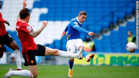 Trossard strikes the ball toward the Manchester United goal.