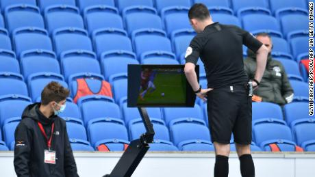Referee Chris Kavanagh checks the VAR screen during the match between Brighton and Manchester United.