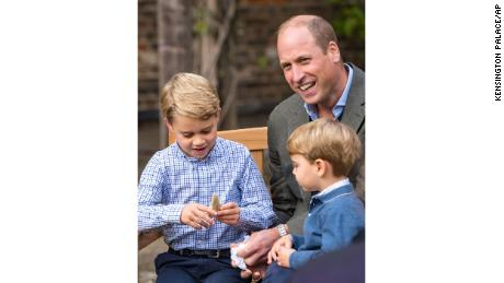 Prince William and Prince Louis examine the tooth of a giant shark given to them by Naturalist Sir David Attenborough in the gardens of Kensington Palace in London.