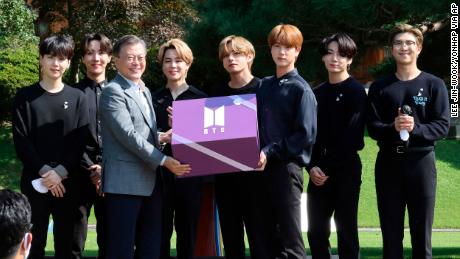 South Korean President Moon Jae-in, third from left, receives a gift from members of South Korean K-Pop group BTS during a ceremony marking the National Youth Day at the presidential Blue House in Seoul, South Korea, Saturday, Sept. 19, 2020.