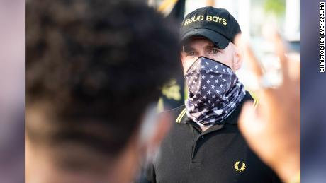 "A man wearing a Proud Boys hat and a scarf bearing the American flag faces off with protestors at a ""Back the Blue"" event in Philadelphia on July 9, 2020."