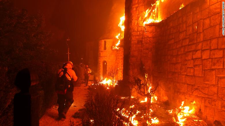 Firefighters walk through the burning Chateau Boswell Winery as the Glass Fire moves through the area on September 27, 2020 in St. Helena, California.