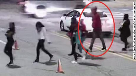 The suspect is said to be about six feet tall and was wearing an orange sweatshirt and jeans. CNN placed a red circle on the image to show the suspect as indicated by the Oakland County Sheriff's Office.