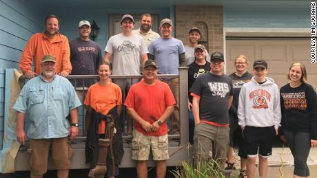 Tim Gjoraas, wearing a black shirt in the front row, stands with the group of volunteers in front of his newly painted house.