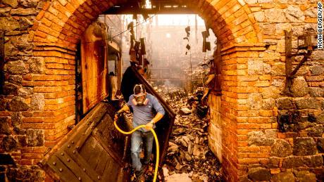 Cellar worker Jose Juan Perez extinguishes hotspots at Castello di Amorosa outside Calistoga on Monday.
