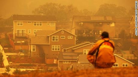 A firefighter looks towards a home that was destroyed by the Glass Incident Fire on September 28, 2020 in Santa Rosa, California.