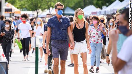 People wear protective face masks while shopping at the Union Square Greenmarket as the city continues Phase 4 of re-opening following restrictions imposed to slow the spread of coronavirus on August 26, 2020 in New York City. The fourth phase allows outdoor arts and entertainment, sporting events without fans and media production.