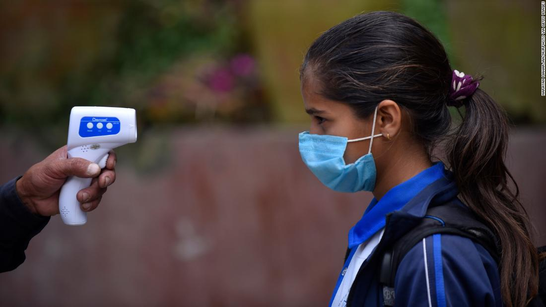 A student has her temperature checked before entering classes at a school in Thankot, Nepal, on September 30.