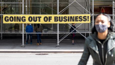 "A woman wearing a mask walks by a ""going out of business"" sign as the city continues Phase 4 of re-opening following restrictions imposed to slow the spread of coronavirus on September 20, 2020 in New York City. The fourth phase allows outdoor arts and entertainment, sporting events without fans and media production. (Photo by Alexi Rosenfeld/Getty Images)"