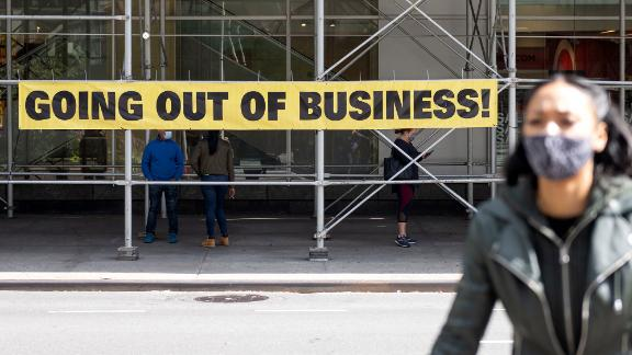 """A woman wearing a mask walks by a """"going out of business"""" sign as the city continues Phase 4 of re-opening following restrictions imposed to slow the spread of coronavirus on September 20, 2020 in New York City. The fourth phase allows outdoor arts and entertainment, sporting events without fans and media production. (Photo by Alexi Rosenfeld/Getty Images)"""