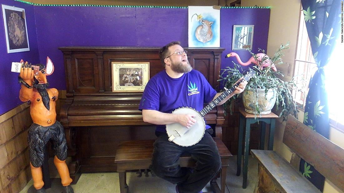 Thorin Thacker, owner of Canyon Cannabis, sings and picks at a banjo on April 11, 2018, at the Gates, Oregon, dispensary. Canyon Cannabis was destroyed by the Beachie Creek Fire on Sept. 8, 2020.