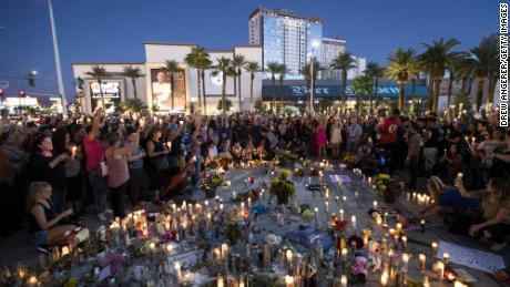 Mourners keep their candles in the air during a moment of silence during a vigil to celebrate a week since the mass shootings at the Route 91 Harvest country music festival.