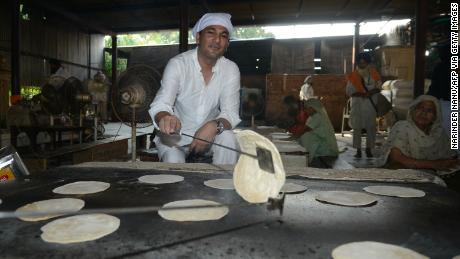 Vikas Khanna, hôte de MasterChef India et chef exécutif du restaurant Junoon à New York, prépare un chappati (pain plat) pour un repas végétarien commun au sanctuaire Sikh Golden Temple à Amritsar le 7 septembre 2016.