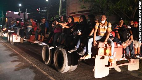 Hondurans sit on the flat bed of a truck as they leave for the US.