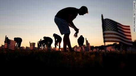 Volunteers with the 'COVID Memorial Project' install 20,000 American flags on the National Mall.