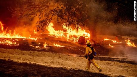 A firefighter passes flames while battling the Glass Fire in a Calistoga, California,  vineyard on Thursday, October 1, 2020.