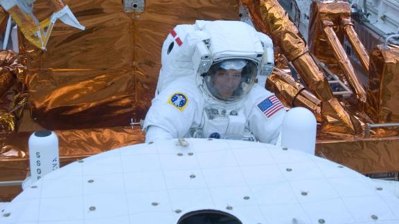 STS-125 Mission Specialist Mike Massimino is pictured here working with the Hubble Space Telescope in the cargo bay of the Earth-orbiting space shuttle Atlantis in 2009.
