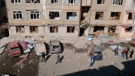 People walk in a residential area of Stepanakert that was allegedly damaged by shelling.