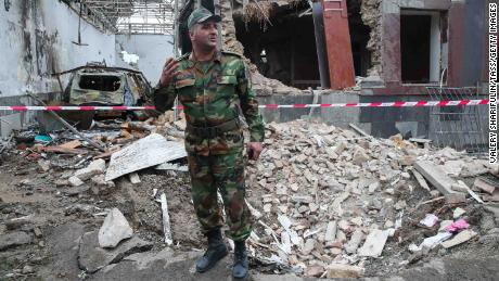 A serviceman stands in front of a building allegedly damaged by shellfire in Gyandzha in Azerbaijan.
