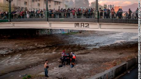 Officer detained for allegedly throwing boy off bridge at a protest in Chile