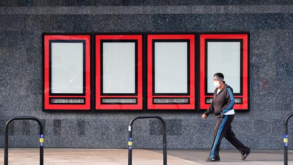 A pedestrian wearing a facemask due to the coronavirus pandemic walks past empty displays where upcoming movies were once displayed as Regal Cinemas L.A. Live on October 5, 2020 in Los Angeles, California. - Regal Cinemas, the second-largest operator of theaters in the United States, plans to close all 500 US theaters affecting some 40,000 employees as the coronavirus pandemic ravages the film industry. (Photo by Frederic J. Brown/AFP/Getty Images)