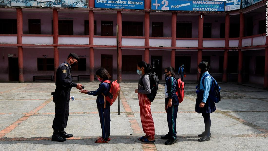 A security guard gives hand sanitizer to students as they arrive at the Prabhat secondary school on the outskirts of Kathmandu, Nepal, on October 6.