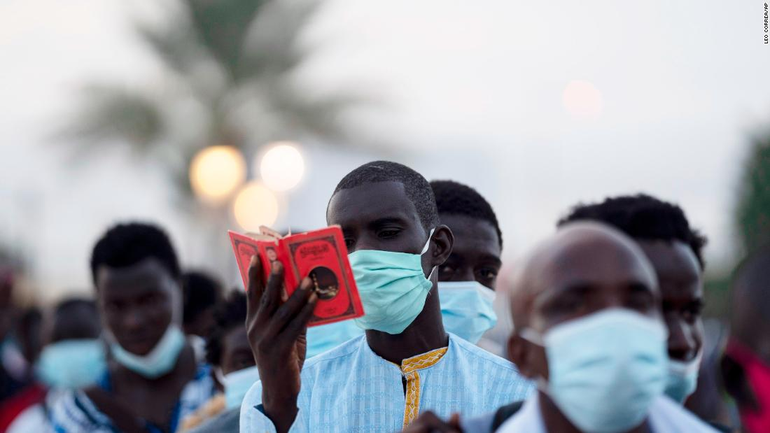 A man from the Mouride Brotherhood reads a book with poems written by Cheikh Amadou Bamba as he stands in line to enter the Grand Mosque of Touba in Touba, Senegal, on October 5.
