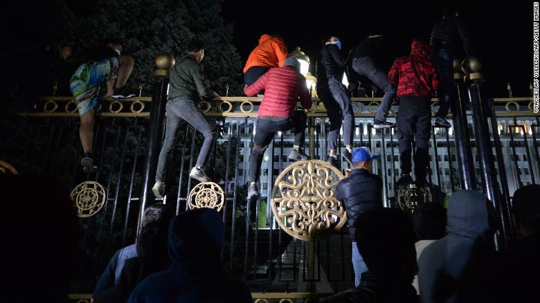 В понедельник протестующие пытаются прорваться через ворота здания правительства в Бишкеке.