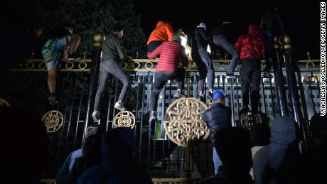 Protesters attempt to break through the gates of government headquarters in Bishkek on Monday.