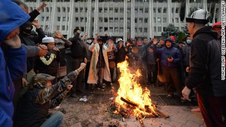 People protesting the results of a parliamentary vote gather by a bonfire in front of the seized main government building, known as the White House, in Bishkek on October 6.