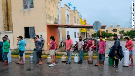People line up to buy gas prior to the arrival of Hurricane Delta in Cancun, Mexico.