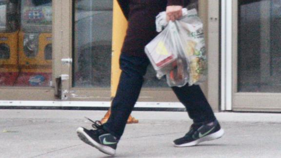 A woman in Toronto carries her groceries in plastic bags on April 24, 2020.