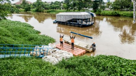 Local workers collect trash collected by the autonomous Interceptor 001 anchored in the Cengkareng Drain waterway in Jakarta, Indonesia.