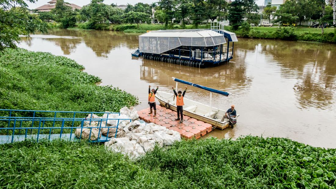 Local workers haul away trash collected by the autonomous Interceptor 001 anchored in the Cengkareng Drain waterway in Jakarta, Indonesia.