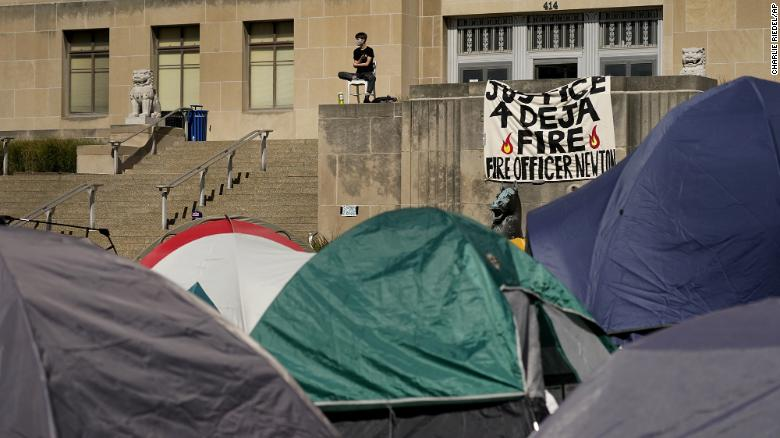 A protester sits overlooking a tent camp in front of City Hall in Kansas City.