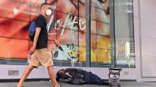 A homeless person sleeps in front of a store at Time Square on September 28, 2020 in New York City.