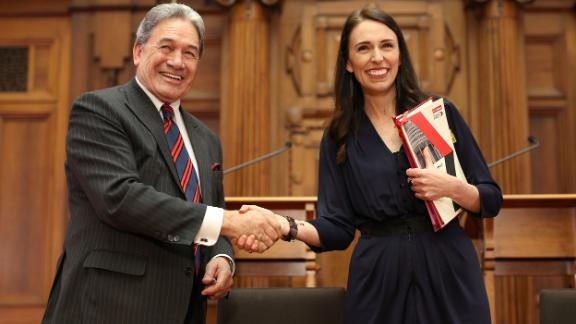 Prime Minister-designate Jacinda Ardern and New Zealand First leader Winston Peters shake hands during a coalition agreement signing at Parliament on October 24, 2017, in Wellington. For weeks after the country's 2017 general election, there was no clear victor, with neither major party winning an outright majority.