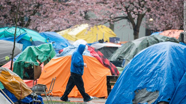 A man walking through a Vancouver tent city in March. Researchers in a new study found that homeless people who received direct cash transfers were able to find stable housing faster.
